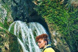 Young woman near a waterfall