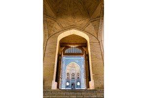 View of Mir-i Arab Madrasa through the doorway of Kalyan Mosque in Bukhara, Uzbekistan
