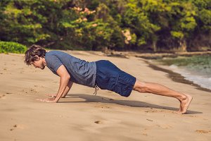 young male working out on beach, sporty man doing exercises