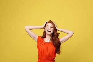 Lifestlye, freedom and happiness concept - Portrait Young beautiful happy girl in orange gorgeous dress showing hand in air. Isolated on bright yellow background