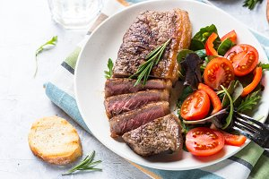 Grilled beef striploin steak with fresh salad.