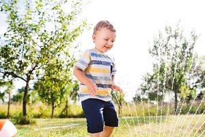 Little boy at the sprinkler having fun, summer garden