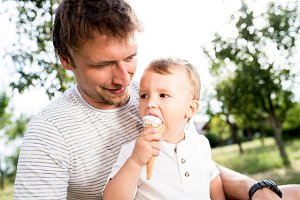 Father and son eating ice cream, sunny summer garden
