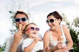 Father, mother and son eating ice cream, sunny summer