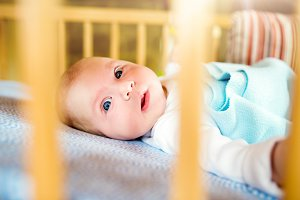 Little baby boy lying in wooden crib, close up
