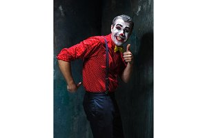 Terrible clown and Halloween theme: Crazy red clown in a shirt with suspenders