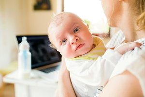 Unrecognizable mother holding baby son, milk in bottle, laptop