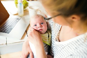 Unrecognizable mother holding baby son, milk in bottle, laptop