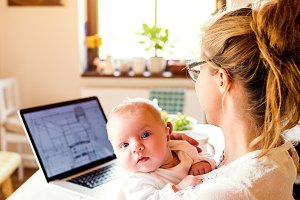 Beautiful mother holding baby son, laptop on table, close up