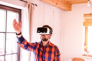 Man wearing virtual reality goggles standing in a kitchen