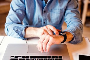 Man working from home on laptop, wearing smartwatch