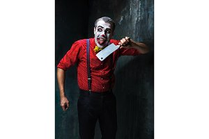 The crazy clown holding a knife on dack. Halloween concept
