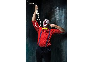 The scary clown and rope for hanging on dack background. Halloween concept