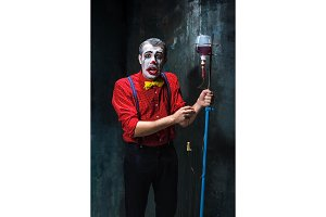 The scary clown and drip with blood on dack background. Halloween concept
