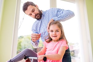 Father with daughter, styling her hair, riding bicycle indoors