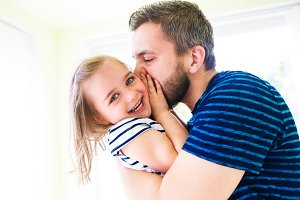 Close up of hipster father kissing his little daughter