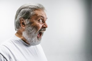 The senior emotional angry man screaming on white studio background