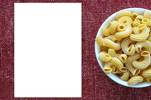 rigati pasta in a white bowl on a red brown cloth burlap background on the side. White space for text and ideas.