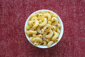 rigati pasta in a white bowl on a red brown cloth burlap background in the center.