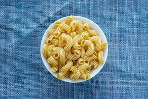 rigati Pasta in a white cup on a blue knitted background in the center.