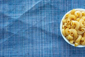 rigati pasta in a white bowl on a blue knitted background with a side. With space for text.