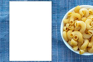 rigati pasta in a white bowl on a blue knitted background with a side. White space for text and ideas.