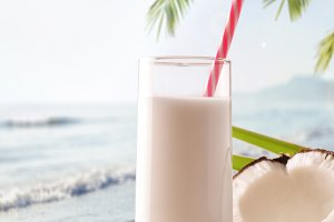 Coconut milk on the beach vertical