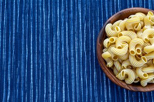 rigati pasta in a wooden bowl on a striped white blue cloth background with a side. With space for text.