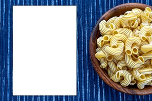 rigati pasta in a wooden bowl on a striped white blue cloth background with a side. White space for text and ideas.