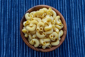 rigati pasta in a wooden bowl on a striped white blue cloth background in the center.