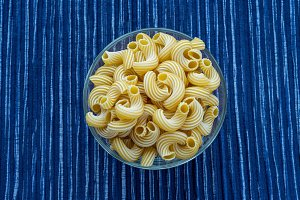 rigati pasta in a glass bowl on a striped white blue fabric background in the center.