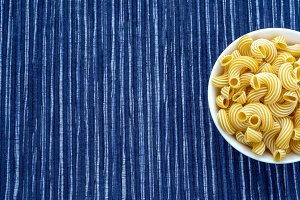 rigati pasta in a white bowl on a striped white blue cloth background with a side. With space for text.