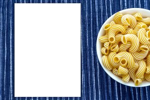 rigati pasta in a white bowl on a striped white blue cloth background with a side. White space for text and ideas.