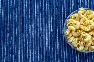 rigati Pasta in a glass cup on a striped white blue cloth background with a side. With space for text.