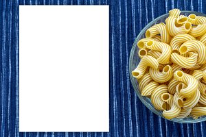 rigati Pasta in a glass cup on a striped white blue cloth background with a side.White space for text and ideas.
