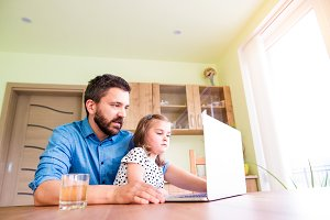 Father and daughter, playing on laptop, sitting in kitchen