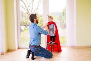 Hipster father with princess daughter in red superhero cape