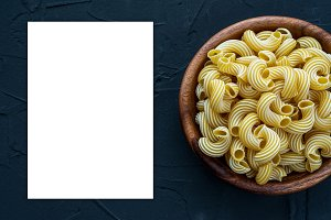 rigati pasta in a wooden bowl on a black textured background from the side. White space for text and ideas.