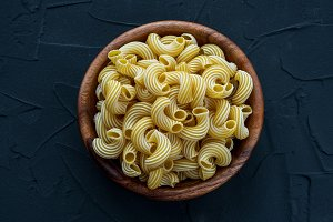 rigati pasta in a wooden bowl on a black textured background in the center.