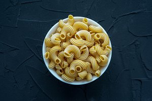 rigati Pasta in a white cup on a black textured background in the center.