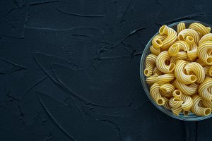 rigati Pasta in a glass cup on a black textured background from the side. With space for text.