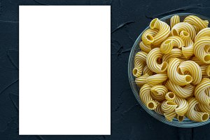 rigati Pasta in a glass cup on a black textured background from the side. White space for text and ideas.