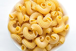 rigati pasta in white bowl on white background in the center close-up with top.