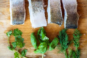 Raw zander fish fillets with various herbs, wooden background.