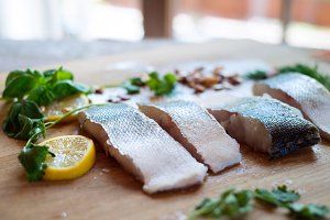 Raw zander fish fillets with lemon slices and herbs.