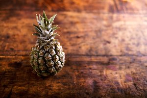Fresh ripe pineapple laid on wooden table, copy space