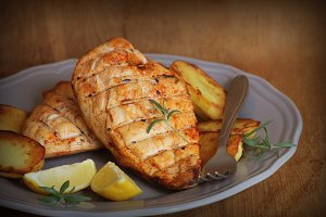 Grilled chicken breast with fried potato and lemon