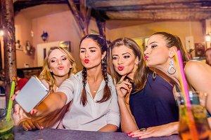 Young beautiful women in bar taking selfie