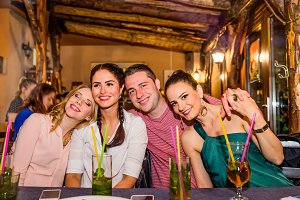 Young beautiful people with cocktails in bar or club