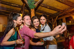 Young beautiful people with cocktails in bar taking selfie